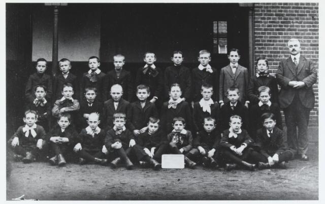 055568 - Onderwijs. Klassenfoto. Meester Jos. van de Lisdonk op de speelplaats van de openbare lagere school aan de Paardenstraat met zijn leerlingen.  Plannen om een nieuwe openbare lagere school aan de Doelenstraat te bouwen, vonden in 1921 geen doorgang, waarnaar door het kerkbestuur aan de Varkensmarkt een katholieke bijzondere lagere school voor jongens gebouwd werd. Deze Petrus Canisiusschool werd op 22 december 1925 geopend. Ondanks protest van de protestanten, werd in dat jaar door raad besloten om de openbare school aan de Paardenstraat te sluiten. dit besluit werd echter door Gedeputeerde Staten teniet gedaan.