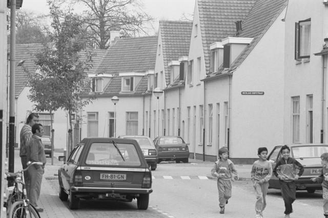 TLB023000016_001 - Gerenoveerde arbeiderswoningen. Volwassenen bij geparkeerde auto's. Kinderen hollen op straat. Foto gemaakt ten behoeve van de Begrotingskrant van Tilburg, waarin wordt aangegeven dat de stad financieel gezond is als gevolg van het Tilburgs Model
