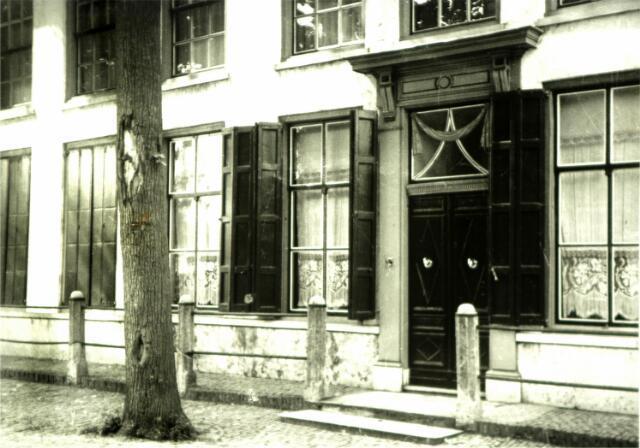 """054715 - Vrijthof nr. 35, het voormalige notarishuis met boven de voordeur de burgemeesterscherp, verwijzend naar maire Martinus Huijsmans die het pand liet (ver)bouwen dat oorspronkelijk bestond uit drie afzonderlijke woonhuizen. Rond 1800 werd een nieuwe voorgevel en kap aangebracht, waarbij afbraakmaterialen van de voormalige schuurkerk zijn gebruikt. Rond 1950 stond het pand bekend als """"het Witte Huis"""" aan Markt nr. 288. In die tijd verkeerde het pand in zeer desolate toestand. Na de bevrijding was de woonruimte gevorderd voor de huisvesting van drie gezinnen en ontstond er enkele keren een binnenbrand. Later werd het pand eigendom van de kerk. Rond 1950 is het gesloopt en vervangen door een nieuwe pastorie onder architectuur van Jos Bedaux. Op 30 september 1950 ging het ministerie van Onderwijs Kunsten en Wetenschappen akkoord met de sloop van het monumentale pand.1"""