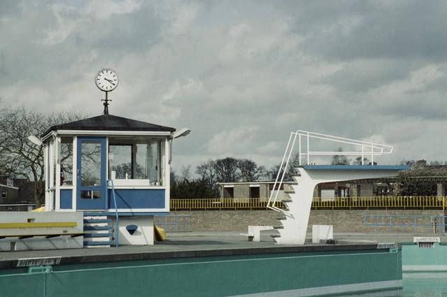 TLB023000059_001 - Openluchtzwembad  Zouavenlaan met badmeesterhuisje en hoge duikplank. Dit zwembad, gelegen aan de toenmalige Berkdijksestraat hoek Zouavenlaan is gebouwd in 1962 en buiten gebruik gesteld op 03/09/1995