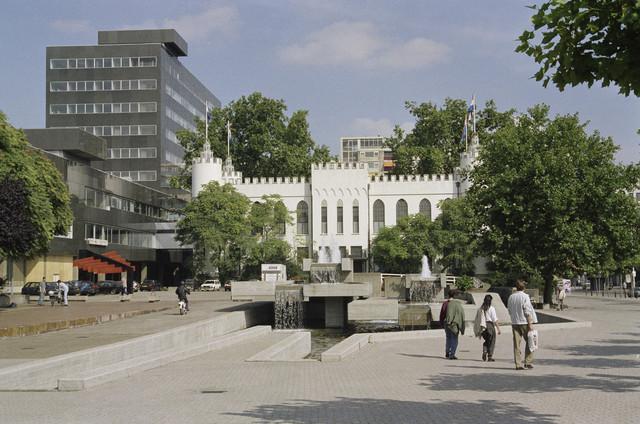 """TLB023000292_002 - Zicht op het oude en nieuwe stadhuis gezien van uit het Willemsplein. Het oude Paleis-Raadhuis werd gebouwd in opdracht van Koning Willem II en heeft verschilldende bestemmingen gehad, t.w. o.a. Paleis, Schoolgebouw en Gemeentehuis. Door ruimtegebrek werd besloten een nieuw Stadskantoor te bouwen, naar ontwerp van Architectenbureau Kraaijvanger. Het nieuwe kantoor, in de volksmond """"de Zwarte Doos"""" genoemd, werd in 1971 opgeleverd. Het oude en nieuwe stadhuis zijn middels een luchtbrug aan de noordelijke flank (linker kant van Paleis) met elkaar verbonden. Op de voorgrond een fontijn naar ontwerp van kunstenaar Joop Beljon (gereed 1972)."""