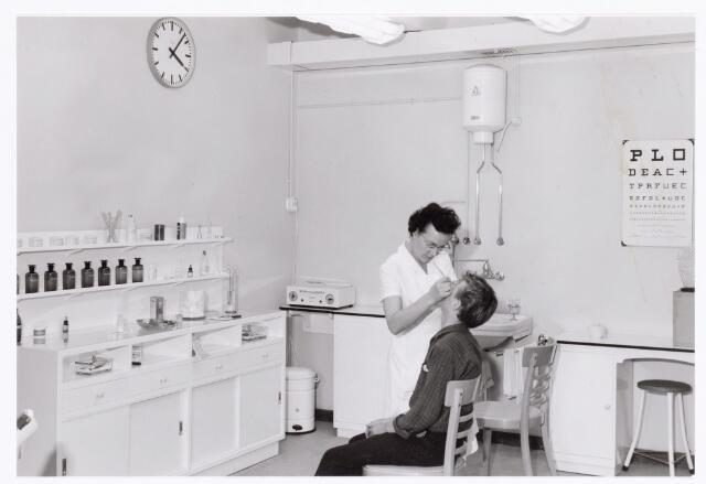 039401 - Volt, Hulpafdeling, Medische Dienst, Verbandkamer. Zuster van Opstal in de behandelkamer van de Medische Dienst op complex Zuid omstreeks 1970.