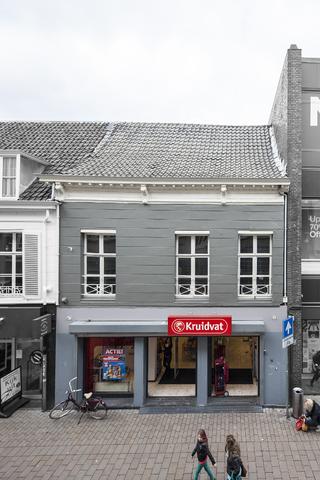 1611_065 - Heuvelstraat in Beeld. Het gebouw is waarschijnlijk van 1815. De eerste familie die er in woonde was de familie Thomas Joseph van Dooren, daarna de familie Perquin en ook de grootvader van L.N. Knegtel woonde er. Op 28.10.1872 kocht Nardus Knegtel dit pand voor fl. 7.850,--. Tijdens de bouw van het nu naastgelegen pand van Peek & Cloppenburg in 1961 werd een muur van dit pand afgebroken en kwam er goudbehang met daaronder kranten uit 1812 te voorschijn met verslagen over een veldslag door Napoleon etc. Nu is er een gestucte gevel met drie ramen die niet symmetrische over de gevel verdeeld zijn en is het 't Kruidvat dat er in te vinden is.