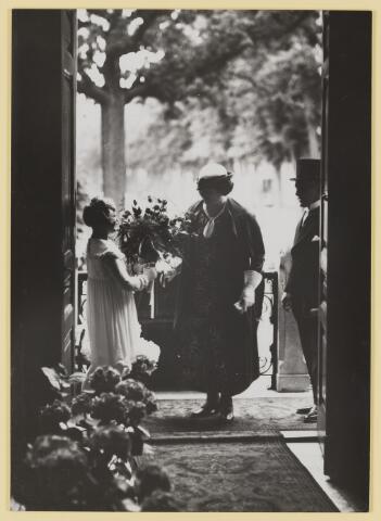 075518 - Het 12 1/2 jarig ambtsjubileum van burgemmeester J. Verwiel op 1 juli 1934. op weg naar de plechtige raadszitting krijgt burgemeestersvrouw bloemen aangeboden.