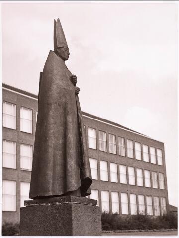 """034294 - Het bronzen beeld """"Il Cardinale (De staande kardinaal) vervaardigd door Giacomo Manzù  (1908-) in het plantsoen van de St. Paulus H.B.S. Het beeldhouwwerk is in 1967 beschadigd en in juli 1977 weer opnieuw geplaatst in de receptiehal van het gemeentehuis."""