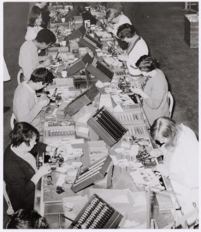 039009 - Volt. Zuid. Condensatoren. Fabricage. Productie. Montage van foliecondensatoren. Hier nog handmontage ( 1960-1970 ).  In 1970 kwam de eerste volledig geautomatiseerde lijn klaar. Foliecondensatoren waren door de toepassing van kunststof als diëlectricum veel kleiner dan de voorheen in gebruik zijnde luchtcondensatoren. Vooral bij draagbare radio's was dat een groot voordeel.