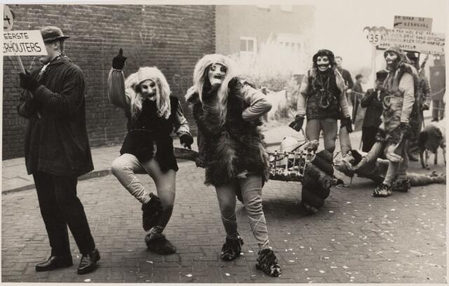 """101344 - Carnaval 1959. Optocht met de groep De Eerste Oosterhouters.De zogenaamde """"Eerste Oosterhouters"""" sleepten hun prooi, een vrouw, mee door de optocht."""