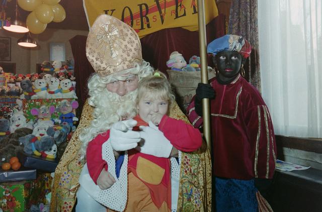 1237_001_003_024 - Feest. Korvel Winkelstraat. Sint Nicolaasviering. Een kind poseert met Sinterklaas en Zwarte Piet tijdens een Sinterklaasfeest georganiseerd door winkeliersvereniging Korvel Vooruit op 27 november 1999. Op de achtergrond staan de cadeautjes.