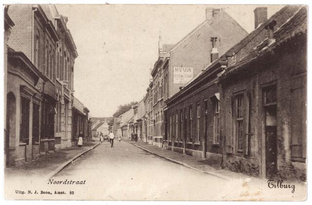 001723 - Noordstraat in noordwestelijke richting. Rechts v.r.n.l. de panden M1067-1063. In het huis met reclame op de zijgevel, M1063, later Noordstraat 82, woonde kleermaker Wilhelmus Faes. De lage huisjes werden rond 1900 vooral bewoond door arbeiders. Achtereenvolgend v.r.n.l. A. van den Brand werkman bij de spoorwegen, de weduwe Meuwese-Baijens, broodbakker C. van den Abeelen en tuinier J.C. Keepen. Rond 1910 zijn deze pandjes, op het pand nr. 84 na, afgebroken en vervangen door nieuwbouw. In het pand nr. 84 woonde rond 1910 de voornoemde J.C. Keepen.