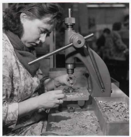 039056 - Volt Zuid. Productie, fabricage van spoelen of correctiemiddelen rond 1960. Hier worden de spoelvoetjes van aansluitpennen voorzien.