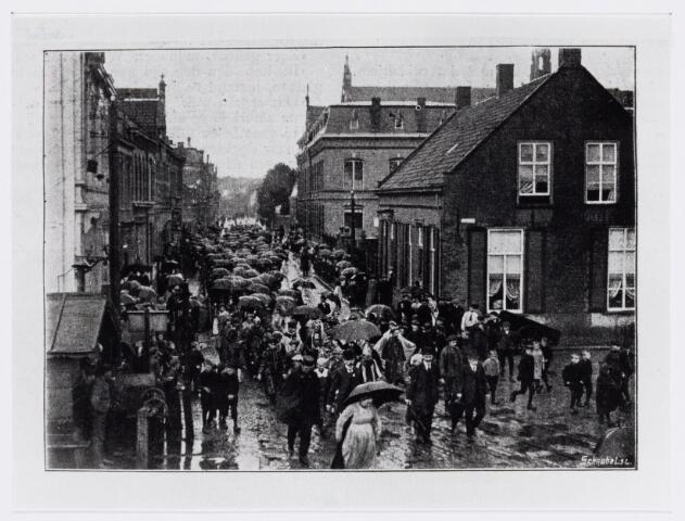 037825 - Textiel. Een stoet van werknemers van wollenstoffenfabriek H. Eras loopt door de straten van Tilburg ter gelegenheid van het gouden jubileum van de stoomfabriek in 1910. Hier is het gezelschap in de Gasthuisstraat (nu Gasthuisring) vlak  bij de overweg