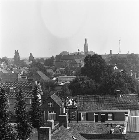 072442 - Op de voorgrond de Dorpsstraat. Op de achtergrond het klooster van de fraters en de toren van parchiekerk St. Jans Onthoofding.