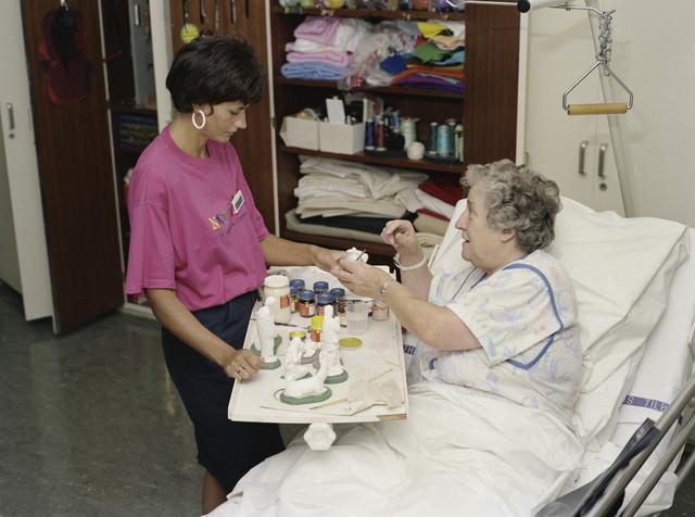 TLB023000091_004 - Welfare afdeling van voormalig Maria Ziekenhuis. Bezigheidstherapeute / Activiteitenbegeleidster helpt patient bij het beschilderen van gipsen beeldjes. Foto ter promotie van opleiding en t.b.v. Onderwijsexpositie.