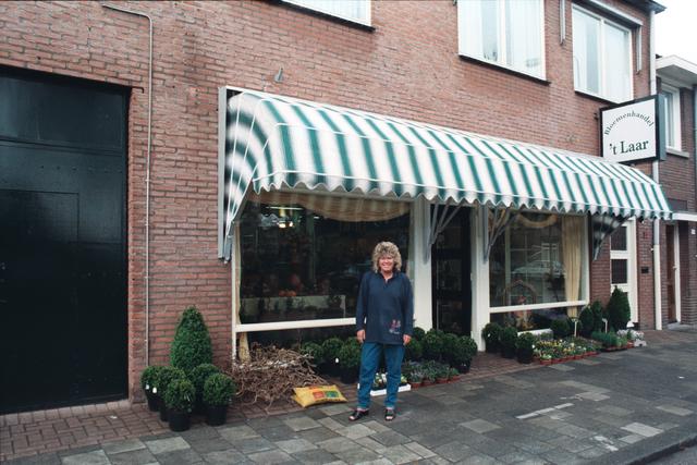 1237_010_757_011 - Ondernemers. Bloemen. Bloemist. De eigenaar van Bloemenhandel 't Laar poseert voor haar winkel in de Tilburgse Laarstraat.