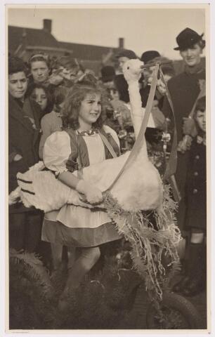 042695 - Meisje met versierde step en ooievaar neemt deel aan de festiviteiten op 1 februari 1938 rond de geboorte van prinses Beatrix