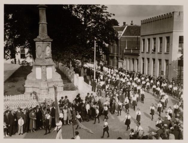 049056 - Raadhuisfeesten. Optocht van Tilburgse verenigingen. Een gymnastiekvereniging die passeerd hier de gedenknaald van Koning Willem II aan de  Paleisstraat. Foto uit ´Je Taalboek´ van frater Victor van Nispen.