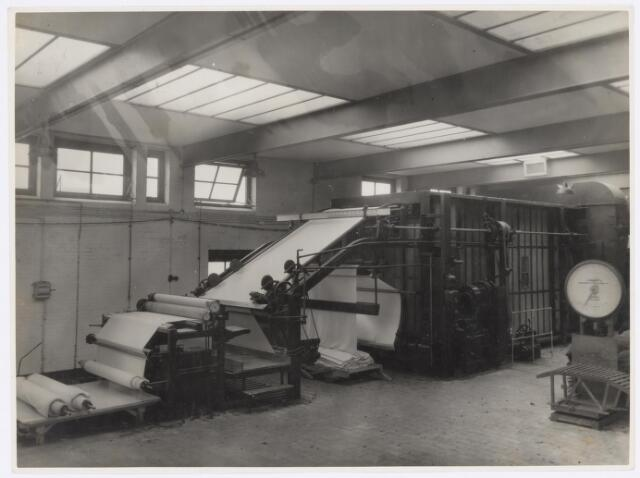 037730 - Textiel. Spanraamdroogmachine in de droogappretuur van wollenstoffenfabriek H. F. C. Enneking. De stukken waren afkomstig uit de natappretuur en moesten worden gedroogd alvorens ze konden worden afgewerkt