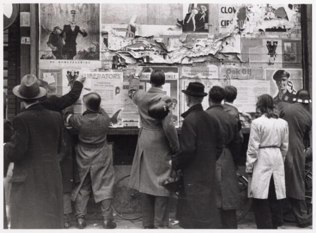 013304 - WO2 ; WOII ; Tweede Wereldoorlog. Bevrijding. Elke Duitse aanwezigheid in het straatbeeld moet worden verwijderd, dus ook aanplakbiljetten en affiches. Op een bord bij de boterhal aan de Markt wordt alles gezuiverd wat aan de voormalige bezetter doet herinneren