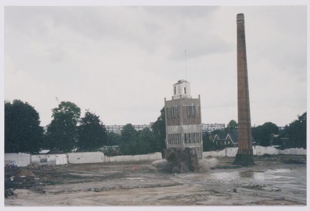 043842 - Het opblazen van de fabrieksschoorsteen en de watertoren op het terrein van de Regenboog aan de Bredaseweg.