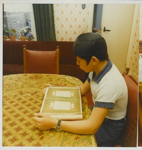 072250 - Turkse jongen lezend in de Koran in een woning aan de Besterdstraat in Goirle.