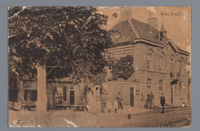 057976 - Gilze. raadhuis/gemeentehuis. Deze zeventiende-eeuwse predikantswoning kwam in 1796 als raadhuis in gebruik. De voorgevel kreeg dit uiterlijk door een verbouwing in 1876. Het gemeentebestuur ruilde het pand in 1921 (na overleg met het kerkbestuur) met het patronaat in de Nieuwstraat. Tijdens de tweede wereldoorlog werd het gebouw verwoest. De eerste woning voorbij het raadhuis liet herbergier Everts bouwen op de plaats van een ouder woonhuis. Rechts het woonhuis, met looierij erachter, Van Hoevenaars-van Poppel. Hierin had notaris le Maire zijn kantoor, doch hij woonde in een deel van het raadhuis. Voor het raadhuis de wachtpost uit 1914/1918.