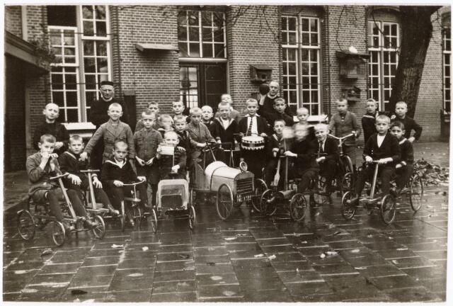 051069 - Jeugdzorg. In 1911 begonnen de fraters van Tilburg met de zorg voor voogdij-jongens vanaf 6 jaar. Hier staan de weeskinderen voor het kleine weeshuis. Daarvoor waren zij ondergebracht bij de zusters karmelitessen van het Goddelijk Hart aan het Wilheminapark. Links frater Winandus Roosen en rechts frater Servatio Adan.In 1948 was de boom verdwenen. Links op de foto waren de toiletten.De deur in het midden gaf toegang tot de speelzaal/eetzaal.