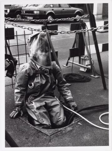 042243 - Riolering. Personeel van Van Hees bezig met het zuiveren en herstellen van de riolering in de Groenstraat ter hoogte van kinderwagenfabriek Mutsaerts. Een medewerker daalt af in het riool