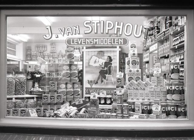 653771 - Middenstand. Etalage J. van Stiphout, VéGé-kruidenier. VéGé stond voor VErkoop GEmeenschap. Dit pand staat op de hoek van de Bredaseweg en de Ringbaan West.