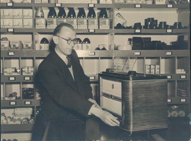 651944 - Volt-zuid.De eerste personeelswinkel van Volt, gevestigd op de gang naast de kantine op de bovenverdieping van gebouw B. De heer Lanslots, de beheerder, demonstreert een radio.