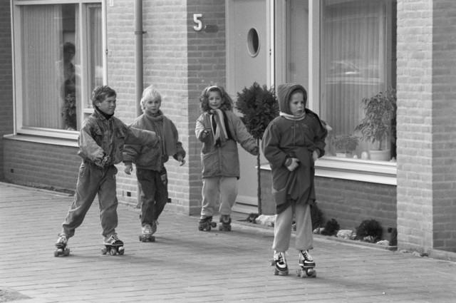 """TLB23000130_004 - Spelende kinderen op rolschaatsen voor een woning in nieuwbouwwijk. Foto gemaakt in kader Reeshof  """"Gezond beleid"""". Van links naar rechts Dennis Fichter, Cristy Fichter, Lizette van den Langenberg, Monique van den Langenberg."""