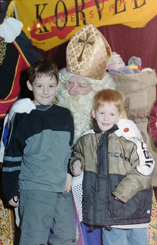 1237_001_003_008 - Feest. Korvel Winkelstraat. Sint Nicolaasviering. Twee jongens poseren met Sinterklaas tijdens een Sinterklaasfeest georganiseerd door winkeliersvereniging Korvel Vooruit op 27 november 1999.