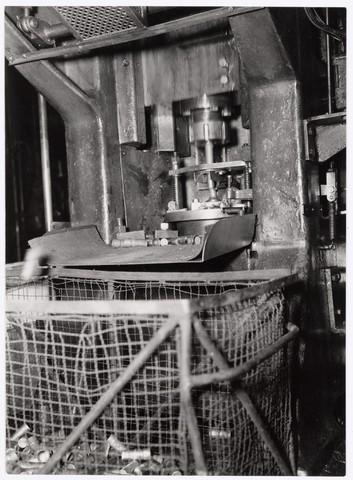 039036 - Volt. Zuid. Productie, fabricage van onderdelen in afd. metaalwaren rond 1950. Hier het extruderen (spuitgieten) van spoelbussen. De gerede producten vielen in de onderstaande mand.