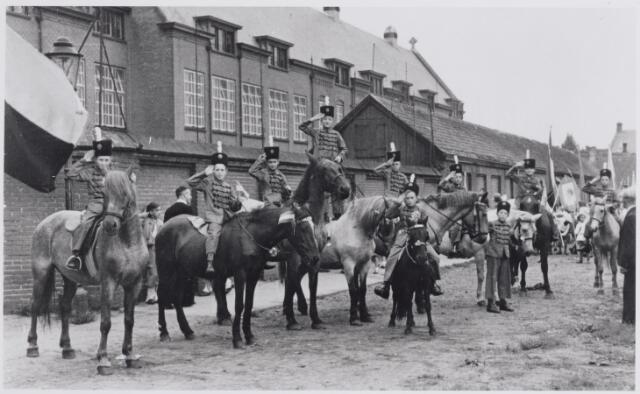 045606 - Oranjefeesten. Thomas van Diessenstraat met op de achtergrond het internaat van de fraters van Tilburg. Op de voorgrond deelnemers aan de koninginnenoptocht.