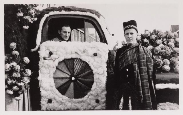043128 - Wol- en bloemencorso b.g.v. het 10-jarig bevrijdingsfeest. Koos Eras in zijn praalwagen met Tweedstoffen.