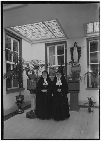 050960 - Enkele zusters van de congregatie van de zusters van liefde van O.L.V. Moeder van Barmhartigheid. LInks het beeld van hun stichter, mgr. Zwijsen, rechts het beeld van het H. Hart.