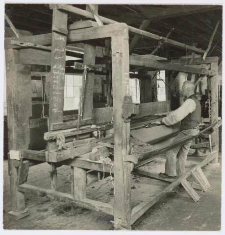 037456 - Textiel. Huiswever M. van Loon aan het werk achter zijn getouw. Dit type werd door de meeste Tilburgse thuiswevers gebruikt. Het afgebeelde exemplaar werd voor het laatst gebruikt tijdens de Nederlandsche Folkloreschouw die van 20 juli tot 5 augustus 1929 in Tilburg werd gehouden