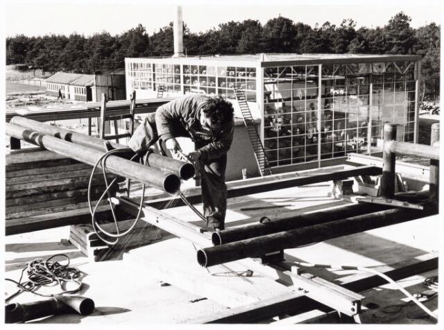 039214 - Volt. Algemeen, Gebouwen, Nieuwbouw t.b.v. de gereedschapmakerij. Laswerkzaamheden op het dak van hal ND op complex Noord in 1964. Op de achtergrond het ketelhuis.