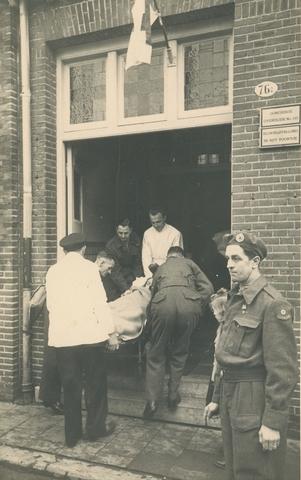 1696015 - Op tweede kerstdag 1949 werd er voor de eerste keer aan een jaarlijks terugkerende traditie begonnen. De transportcolonne organiseert een kerstfeest voor bedlegerige zieken en invaliden in het Katholiek Militair Tehuis aan de Capucijnenstraat. Een zieke op brancard wordt door een deuropening getild.