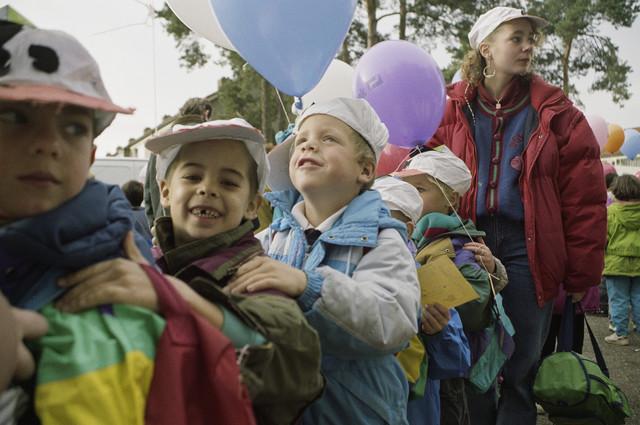 TLB023000382_003 - Hossende kinderen en begeleiders bij de opening van de Karen Weening speeltuin. De Karen Weening speeltuin is een buitenspeeltuin in een bosgebied van 10.000 m², is prachtig aangelegd en wordt door een groep vrijwilligers uit de wijk i.s.m. Contour de  Twern beheerd. De speeltuin is vernoemd naar de winnares van de ontwerpwedstrijd voor een speeltuin in Tilburg