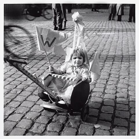 012191 - WO2 ; WOII ; Tweede Wereldoorlog. Bevrijding. Zelfs de allerkleinste Tilburgers deelden op 9 mei 1945 in de feestvreugde, zoals dit meisje in haar versierde kinderwagentje