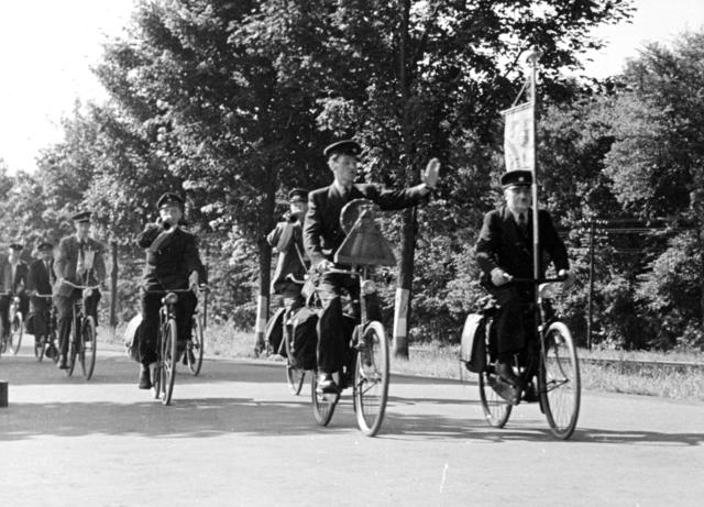 656384 - Kerkelijk erkende fietsbedevaart Tilburg-Kevelaer in 1952. Vertrek uit Kevelaer. A. van Greunsven rijdt voor het eerste het Maria beeldje en Harry de Loos het vaantje.