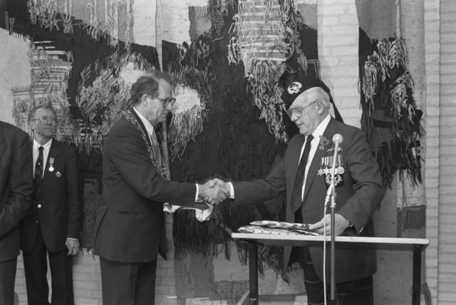 TLB023000114_002 - Tijdens de Bevrijdingsfeesten in 1989 schud Burgemeester Brokx de hand van een gedecoreerde veteraan.