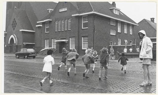 90512 - Made en Drimmelen. Overstekende kinderen in de Zuideindsestraat te Stuivezand. De school ligt aan de overzijde van de straat. Achter het Elisabethklooster (op de foto in het midden). Geheel links de St. Blasiuskerk.