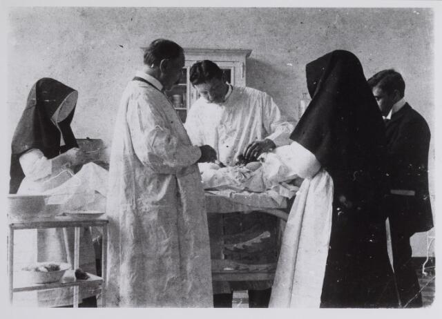 041667 - Elisabethziekenhuis. Gezondheidszorg. Ziekenhuizen. Operatiekamer van het St. Elisabeth Gasthuis op de Locht. De artsen van links naar rechts zijn chirurg J.J. Passtoors, chirurg en huisarts L.J.M. Eijgenraam (met vadermoordenaar). De laatste fungeerde vermoedelijk als narcotiseur, de Zusters van Liefde als operatieassistenten.