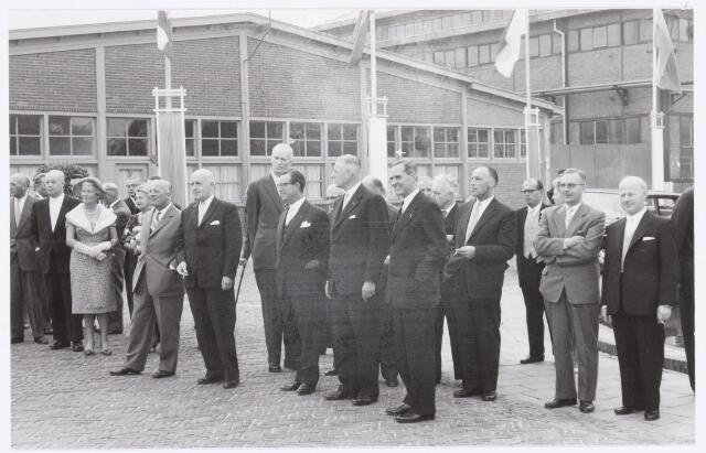 039115 - Volt, zuid. Jubileum. Het 50-jarig jubileum van Volt in 1959. Voor de linkse vlaggenmast wethouder J.C. Baggerman (1910-1983) met daarachter  mevr. Kipperman en Rutten, afd. chef gereedschapmakerij. Vervolgens naar rechts: NN, Dr. Bruyel, burgemeester mr. C.J.G. Becht, ir. Tromp, ir. Frits Philips,  ir. Meijer, toekomstig directeur van Volt met cigaret, NN en Geerts hoofd productiebureau ook met cigaret en flaartje in de bovenzak. Productie-bureau werd later materials management genoemd.
