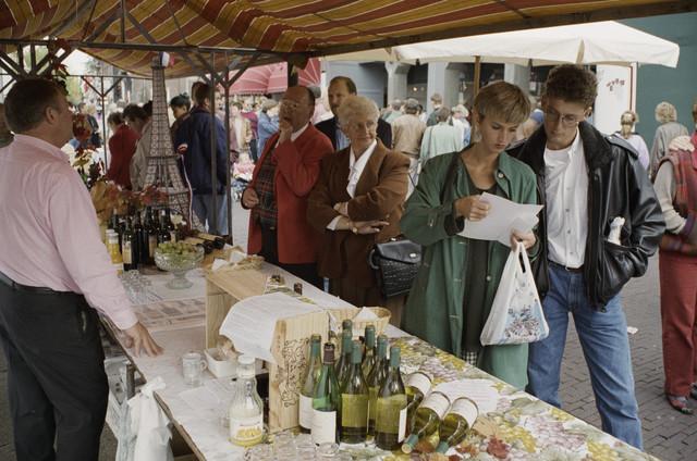 TLB023000251_002 - Stichting Tilburg Wijnstad organiseert  jaarlijks een evenement dat bestaat uit een 'ommegang' van wijnbroederschappen, een oogstdankmis in de Heikese kerk en een wijnstraatje. De Emmapassage is jaren hiervoor gebruikt. Ook op andere plaatsen in het centrum van Tilburg stonden kraampjes waar men kon proeven en kennismaken met de diverse wijnen.  Het evenement is gebaseerd op het feit dat in Tilburg vanouds grote wijnfirma's gevestigd waren, zoals Wijnkopers Verbunt en André Kerstens. Aan het einde van de jaren zestig van de vorige eeuw werd de naam Tilburg Wijnstad al bedacht om Tilburg op een andere manier onder de aandacht te brengen dan als Textielstad.