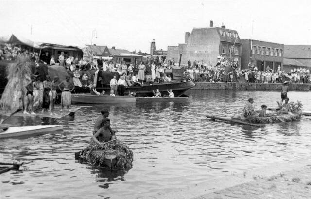 """064764 - Odulphus. De Piushaven op zaterdag 1 juli 1950. Door een actie, gestart door de missieclub van het St. Odulphuslyceum kon een motorboot worden aangeschaft voor pater Meuwese, missionaris in Nieuw Guinea. De overhandiging van de boot, genaamd St. Odulphus-Tilburg, ging met veel plechtigheid gepaard. Bij de haven waren aanwezig mgr. Vrakking, bisschop van Surugao en de Philippijnen, burgemeester en wethouders van Tilburg, de provinciaal overste van de missionarissen van het H. Hart, deken Nabuurs, verkenners en zeeverkenners uit Arnhem, de missieclub van het Odulphuslyceum en  pater Meuwese in eigen persoon. De nieuwe motorboot voer de Piushaven in, omringd door prauwen, bemand door """"vreselijke wilden"""": leden van de Tilburgse kanovereniging. Na de inzegening van de boot door mgr. Vrakking werd het Wilhelmus en het schoollied van St. Odulphus gezongen. De boot lag later ter bezichting in het botenhuis aan de Zwaaikom bij de Oisterwijksebaan. Er stond een collectebus bij om de missie van pater Meuwese te steunen."""