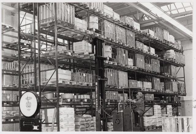 """050175 - Volt, Hulpafdelingen, Centraalmagazijn. Vooruitlopend op de bouw van een geheel nieuw magazijn in Noord, werd in 1976 een noodmagazijn in gebruik genomen op complex Zuid. In de ruimte waar vroeger de gereedschapmakerij was gehuisvest kwamen: expeditie, pakkerij, centrale ontangst en centrale controle. In drie van de vier """"O""""hallen kwam opslag. Een laad- en losruimte werd gekreëerd via het slopen van de gebouwen G en H daterend uit 1928. De bedoeling was ook een proefterrein te zijn om ervaring op te doen voor het nieuwe magazijn in Noord. De ingebruikname was in feite het ontstaan van een nieuwe afdeling """"Goederenbeweging"""" of Physical Distribution. Hierin gingen op de magazijndienst, de pakkerij, groepage, expeditie en vervoer."""