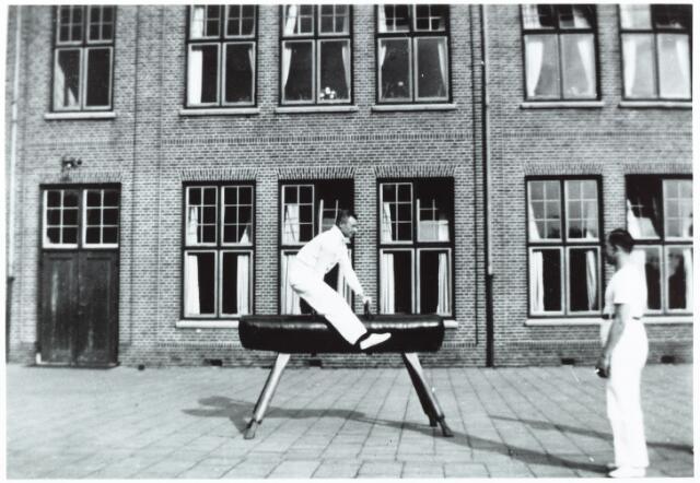 052761 - Sport. Gymnastiek. Gymnastiekvereniging David; op de speelplaats Elzenstraat; op de bok Bertus van Gulick en rechts Piet Hooijen