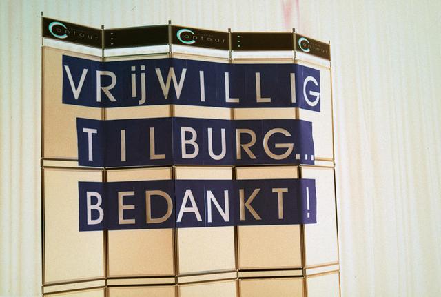 """1237_001_036_001 - Zorg. Bij Contour worden in december 1999 de stimuleringsprijzen voor vrijwilligerswerk uitgereikt. Bord met de tekst: """"Vrijwillig Tilburg bedankt!""""."""
